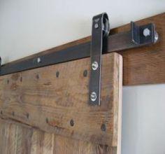 Utiliser les portes comme élément décoratif, c'est possible avec les portes coulissantes sur rail métallique : récupérées ou sur mesure.