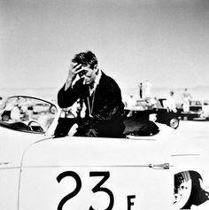 "``It shows a very candid moment of Dean, sitting on the driver's seat molding inside his 23F Speedster, in his trademark ""Zen Meditative"" pose, his right hand on his forehead, eyes closed, as he psyches himself up for the upcoming race. His cigarette dangles from his mouth as he wears a stopwatch attached to a rope around his neck and his iconic racing overalls.``"