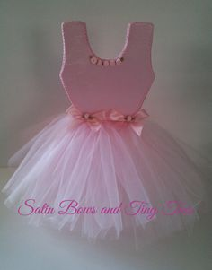 This precious little pink ballerina tutu dress centerpiece will make a beautiful accent to your ballerina themed party, shower or nursery decor. They are double sided and beautifully embellished with satin ribbon roses, trims and layers of tulle . They are free standing and will add the perfect touch to your ballerina theme. They come in 2 different Styles, with or without sleeves. They are absolutely adorable and will wow your guests. Measurements: Stands approximately 15 Tall