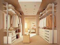 Walk through closet to bedroom with white furniture and brown wall