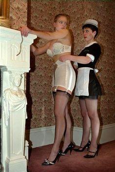 French Maid Helping Mistress Into White Open Bottom Garter Girdle White Strapless Bra Sheer Black Stockings and Black High Heels