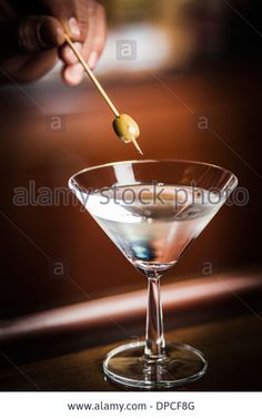 One glass of famous Classic Cocktail Dry Martini with Olive, shot on location on wooden Bar. Bartender inserting Olive. Stock Photo