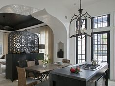 Moroccan kitchen features gothic lantern over black island topped with concrete countertop fitted with gas cooktop and oven alongside an iron and wood dining table surrounded by woven dining chairs. Moroccan Kitchen, Modern Moroccan, Moroccan Style, Kitchen Paint, Kitchen Decor, Kitchen Ideas, Kitchen Design, Decorating Kitchen, Kitchen Walls
