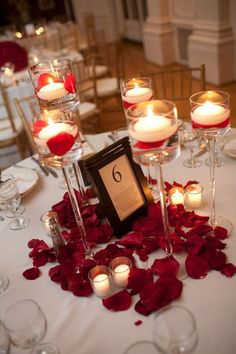 Candle centerpieces with rose petal accents. I don't know about red, but I like this. its simple and romantic.