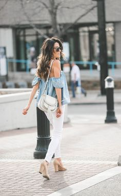 A denim off-the-shoulder top with slim jeans, a saddle bag, and suede pumps
