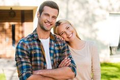 Happy young couple. Happy young couple bonding to each other and smiling while standing against their new house