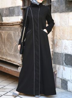 This jilbab is stylish, sophisticated, and practical. Modern, yet subtle; simple without being dull; it strikes the perfect balance in utility and taste that you've been looking for. We love the contemporary details- the cozy high collar, pop of color in the trim and practical pockets.