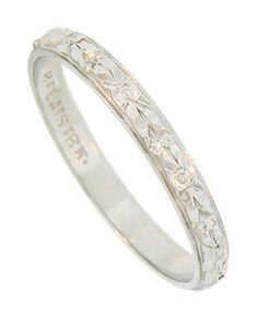 Deep cut floral engraving encircles the face of this 18K white gold vintage wedding band, while delicate milgrain decoration frames the sparkling flowers. The Retro Modern wedding ring measures 2.43 mm in width. Circa: 1930. Size 6 1/4. We cannot re-size.