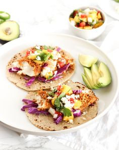 Crunchy Coconut Fish Tacos topped with a fresh mango salsa are the perfect tacos for a Cinco de Mayo fiesta or any time of year! They're baked, not fried, so you can indulge healthfully. | via livelytable.com