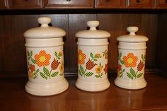 Set of graduated McCoy flowered canisters.