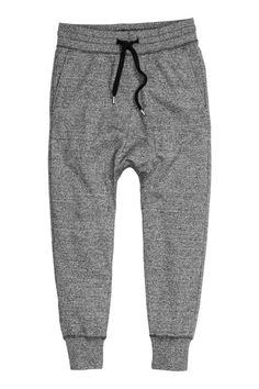 Trainingsbroek: Een broek van joggingstof met een laag kruis en smal toelopende pijpen met een boord onderaan. De broek heeft elastiek en een trekkoord in de taille, steekzakken en een achterzak.