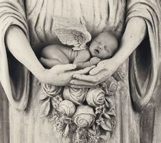 newborn baby cupped in angels hands,  sweetness