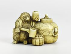 Netsuke of carved ivory, the Tea-kettle Raccoon-dog (Bunbuku Chagama) sitting beside a tea-kettle wearing a coat, holding a ladle and a cup, unsigned: Japan