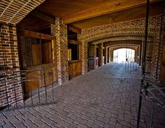 Equestrian life. High style horse barn. Pavers for the floor, wrought iron gates, brick columns and arches.