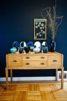 Dark blue walls with white accents and various blue glass accessories