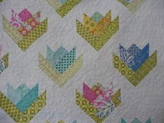 Tulip (AKA Lily) Quilt - Pattern is in Jelly Roll Quilts by Pam & Nicki Lintott (called Floral Bouquet block) or there are free paper-pieced patterns all over the web, e.g. http://nonniequiltingdreams.wordpress.com/2010/12/29/adventures-in-paper-piecing/