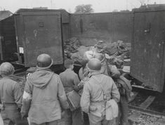 Soldiers of the 45th U.S. Infantry Division compel young men belonging to a chapter of the Hitlerjugend, or Hitler Youth, to view one of many railway cars filled with corpses on the grounds of Dachau.