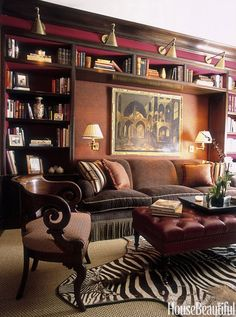 """""""Red libraries are best!"""" says designer Alessandra Branca. Walls are upholstered in wool paisley. The sofa and ottoman are Branca designs.   - HouseBeautiful.com:"""