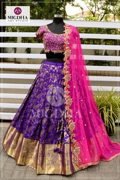Fuchsia pink paired up with dark Violet pattu lehenga to get the vibrant effect and bold golden pasley and florals embroidered all over work. Now available on MugdhaArtStudioFor Order (or) EnquiryWhats app 8142029190 / 9010906544 21 September 2018 Lehenga Saree Design, Half Saree Lehenga, Lehenga Gown, Lehnga Dress, Bridal Lehenga Choli, Lehenga Designs, Anarkali, Banarasi Lehenga, Bollywood Lehenga