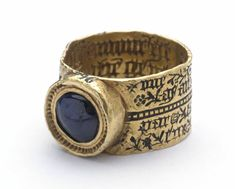 15th C. Love-ring; gold; engraved; broad flat hoop divided horizontally by milled band, inscription on exterior, inscribed interior depicts woman and squirrel among flowers and foliage; circular bezel containing sapphire bead.