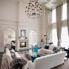 Double height living room with traditional moldings and glass chandelier