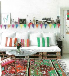 Kilim rug, kitsch bunting and repurposed crates used to create a rustic boho lounge. Pretty bohemian living space.