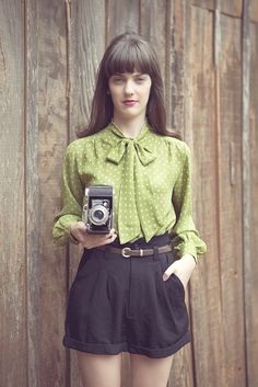 vintage apple green dotted blouse and black high waisted shorts.