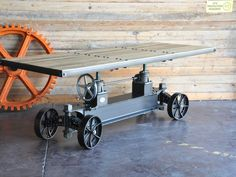 Train Table Wood — Built as a unique dining table, the Train Crank Table gives homage to the train cars and mining carts of yesteryear.  The table top adjusts in height from 30″ dining height to 42″ bar height by cranking the wheel and activating the two 5-ton screw mechanisms.  It can also run on an optional in-floor track for a piece that's truly original and surprising in table design.