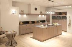 Landelijke keuken met blauwe hardsteen. Deze landelijke keuken brengt door het gebruik van massieve houten keukenkasten en deurtjes de warme en landelijke sfeer boven. Het materiaal van het werkblad is blauwe hardsteen, wat het landelijke naar een hoger niveau tilt. Het keukeneiland is voorzien van een gootsteen, terwijl de kookplaat zich op het werkblad aan de muur bevindt.
