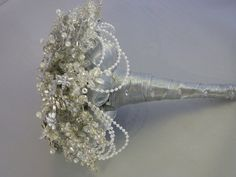 A stunning bouquet that shimmers with 1920s style. It contains beautiful jewelled and mirrored flower brooches as its centrepiece and is