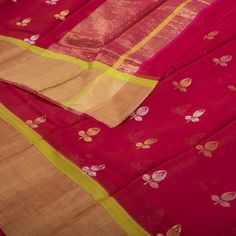 """The """"Dark Red""""#handwoven Chanderi Silk Cotton Sari from Parisera is woven with gold and silver zari floral motifs all over the body that is set off by a gold zari border on either side. An attractive gold zari adorn the Red pallu. The border is repeated on the light red blouse that completes the sari."""
