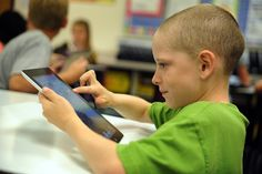 Fourth grader William Ramirez, 9, uses an Apple iPad during the first day of the 2013-2014 school year Aug. 1 at Falcon Elementary School in Falcon School District 49. The elementary school received 230 iPads for a Falcon Zone one-to-one pilot program. Each student in third though fifth grades will receive the tablet, which, save for a signed parent agreement, they'll be able to take home.