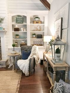 Farmhouse Living room decor with console table, lighting, lanterns, bookcase decor, grey tufted chair, chunky knit throw, white oak side table, wall decor, natural rug.
