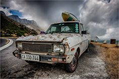 Surfer Transport by Chris Pienaar A year or so ago I drove the pass around Chapmans Peak  and As I was about to enter Houtbay, I came across this old Nissan 1400 LDV that is kept on life support and given character using cable ties and limpet shells. For those not in the know, the Datsun 1200 and its later version the Nissan 1400 are legendary , do not die vehicles used by many students, delivery and courier companies, passed down from dad to son to grandson vehicles.