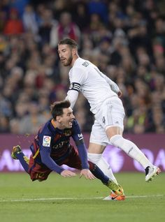 """Barcelona's Argentinian forward Lionel Messi (L) clashes with Real Madrid's defender Sergio Ramos during the Spanish league """"Clasico"""" football match FC Barcelona vs Real Madrid CF at the Camp Nou stadium in Barcelona on April 2, 2016."""