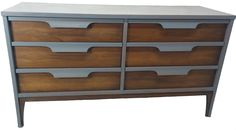 This dresser from Johnson Carper's Fashion Trend collection has been beautifully refinished with a semi-transparent silver grey stain that contrasts beautifully with the walnut accents and formica top. Each of its six drawers, which are decorated with sculpted pulls, works smoothly. It can be sold with its matching tallboy dresser that is also listed. The condition is excellent with only minor wear consistent with its age and history.   Dresser Dimensions: 54ʺW × 18ʺD × 30ʺH