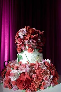 The couple's wedding cake featured two tiers covered with hundreds of pink and red sugar roses and a middle tier decorated with hand-drawn roses and florals. Photography: Lauren Ross Photography & Nancy Cohn Photography. Read More: https://www.insideweddings.com/weddings/sophisticated-breakers-wedding-with-pink-florals/335/