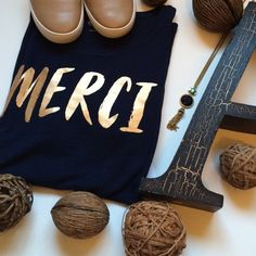 GAP Merci Tee New with tags. This is a fun top! Merci in a gold metallic on the front. Navy blue, short sleeves. Comfy and perfect with jeans! Never worn. Price is firm. GAP Tops Tees - Short Sleeve