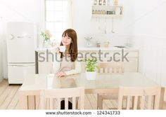 Beautiful asian woman in the kitchen - stock photo