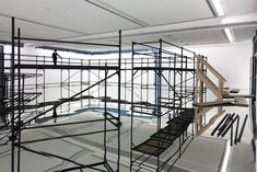 The exhibition pavillion designed by the Irish artist Stephen Craig is set inside an old factory building. The floor of the pavillion is covered entirely with mirror glass and a black spray-painted scaffolding is installed on top of the fragile surface. The modernistic