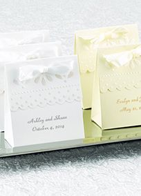 """Guests will be delighted to receive this fabulous favor box filled with candies, truffles or other goodies. Favor boxes are decorated with an embossed pearl design and frilly, scalloped edge. It is recommended to use wrapped candies or liners when placing food into any type of favor box or container.  Features and Facts:   3"""" x 1 7/8"""" x 3 1/4""""  Pack of 25  Some assembly required  Satin ribbon included  Personalization: Enter two lines of personalization such as bride and groom's names on one…"""