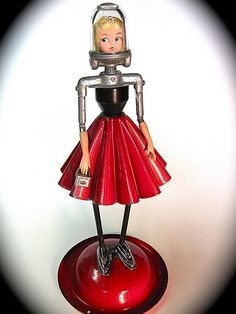 Miss Galaxy Girl found object sculpture made from a vintage christmas tree stand for the skirt and base, 50's hairpin table leg, drum set lugs, 50's auto fuel filter, 60's doll head fro a nurse doll, vintage part of a cord reel for shoulders and some doll hands, and I have no clue what her purse was.