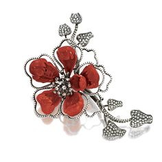 RED CORAL AND DIAMOND BROOCH Modelled as a single flower, the petals composed of carved red coral, the centre set en tremblant with a cluster of rose-cut diamonds, embellished with diamond-set swirls, the stem and leaves pavé-set with rose-cut diamonds, the diamonds together weighing approximately 6.10 carats, mounted in 18 karat blackened gold.