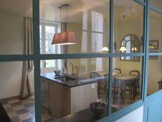 Façon atelier, le cuisine joue la carte de la transparence derrières de jolies portes vitrées sur mesure, en acier peint. Et la couleur bleue, comme un leitmotiv, fait le lien entre le premier et le second niveau d'habitation.