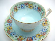 Beautiful antique tea cup and saucer made by Aynsley England Blue tea cup set with blue, pink and yellow flowers. Both pieces are embossed. The backstamp date this cup 1934 - 1939 The rims are gilt. Cup Measures: 2 3/8 high & Saucer Measures 5 3/8 diameter Good conditon, no chips,