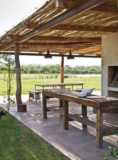 Galería de una casa de fin de semana con parrilla, bancos y mesas de tablones rústicos; piso de cemento y lámparas galponeras en color negro.