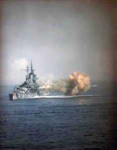 USS Idaho (BB-42) Fires the 14/50 guns of Turret Three at nearly point-blank range, during the bombardment of Okinawa, 1 April 1945