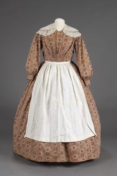 Description Woman's work dress, of printed cotton calico, paisley pattern in red, brown and tan. Long tapered sleeves, body lined with muslin closed by 14 brass hook and eyes, open front, below waist on front with two panels of tight gathers (like smocking), high waist, gathered all around waist, ankle length full skirt. Comment Found in attic of Sheldon Tavern Category Personal Artifacts Date Made ca. 1830