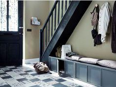 Déco chic et sobre pour cette entrée au style 1930. L'espace sous l'escalier à été astucieusement aménagé pour y installer un vestiaire avec porte-manteaux et casiers de rangement Mixxits pour les chaussures.