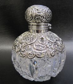 BIRMINGHAM STERLING AND CUT GLASS INKWELL, rounded clear cut glass having Sterling hinged lid, with gilt interior, and intricate Sterling openwork over shoulders. Hallmarked British Sterling, year 1893, with the Silversmith's mark on lid.